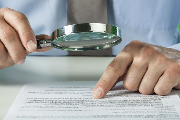 man reading the fine print on a liability waiver with magnifying glass